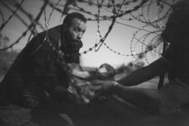 """World Press Photo of The Year Warren Richardson, Australia Hope for a New Life. Un uomo passa un bambino sotto il filo spinato al confine tra la Serbia e l'Ungheria a Röszke, in Ungheria, 28 agosto 2015. (www.worldpressphoto.org/collection/photo/2016"""">World Press Photo)"""